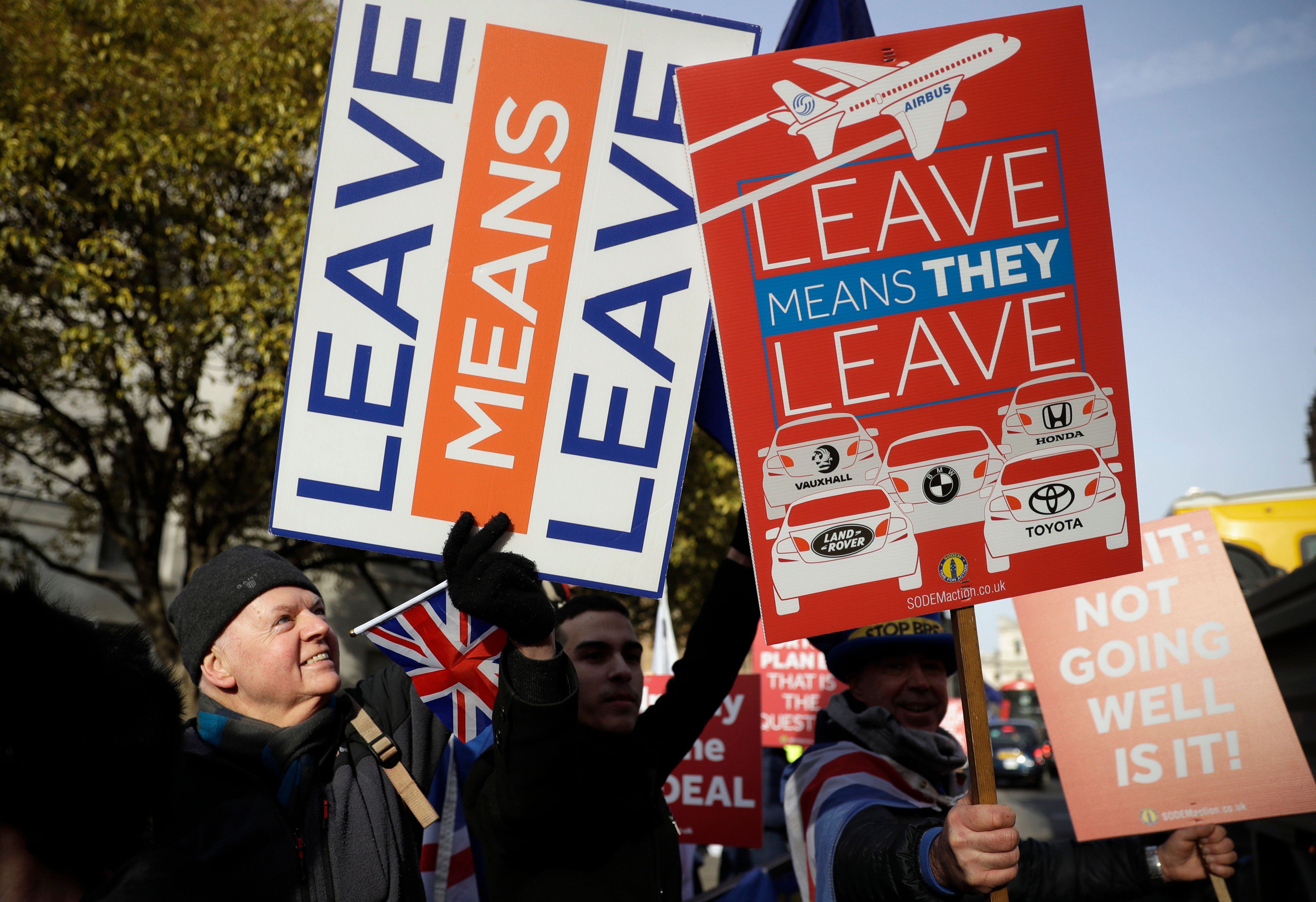 Pro-Brexit, left and anti-Brexit protesters hold banners in London, Tuesday, Jan. 29, 2019. With Britain's House of Commons bitterly divided on the way forward for Britain's departure from the European Union, lawmakers representing various factions are vying to have their say in the Brexit process after they overwhelmingly rejected the government's divorce agreement two weeks ago. (AP Photo/Matt Dunham)