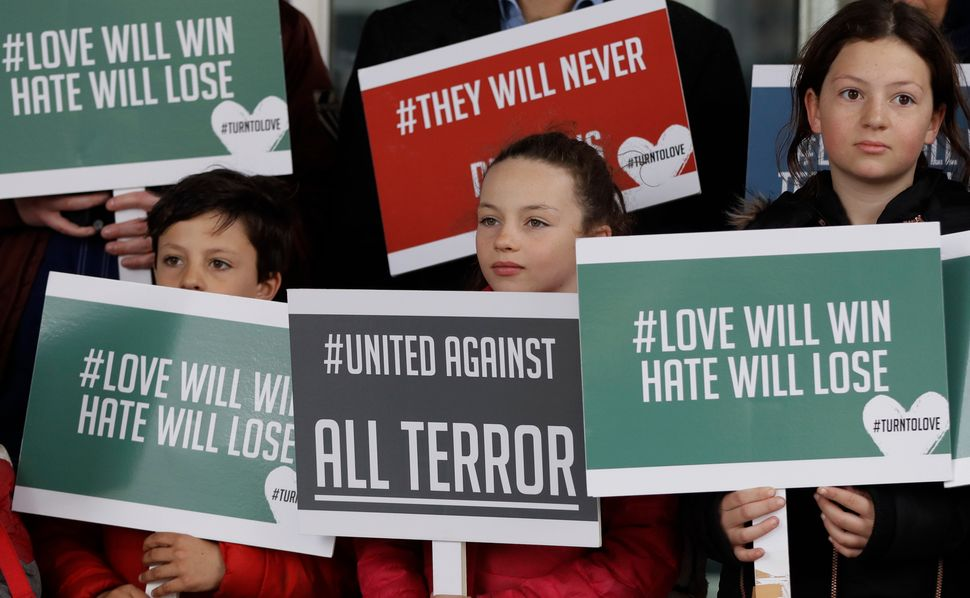 Young demonstrators hold banners from the multi-faith group Turn to Love during a vigil at New Zealand House in London.