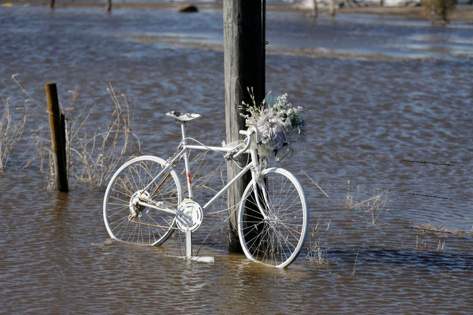 A painted bicycle sits in flood water in Waterloo, Neb., Wednesday, March 13, 2019. Forecasters say major flooding is likely