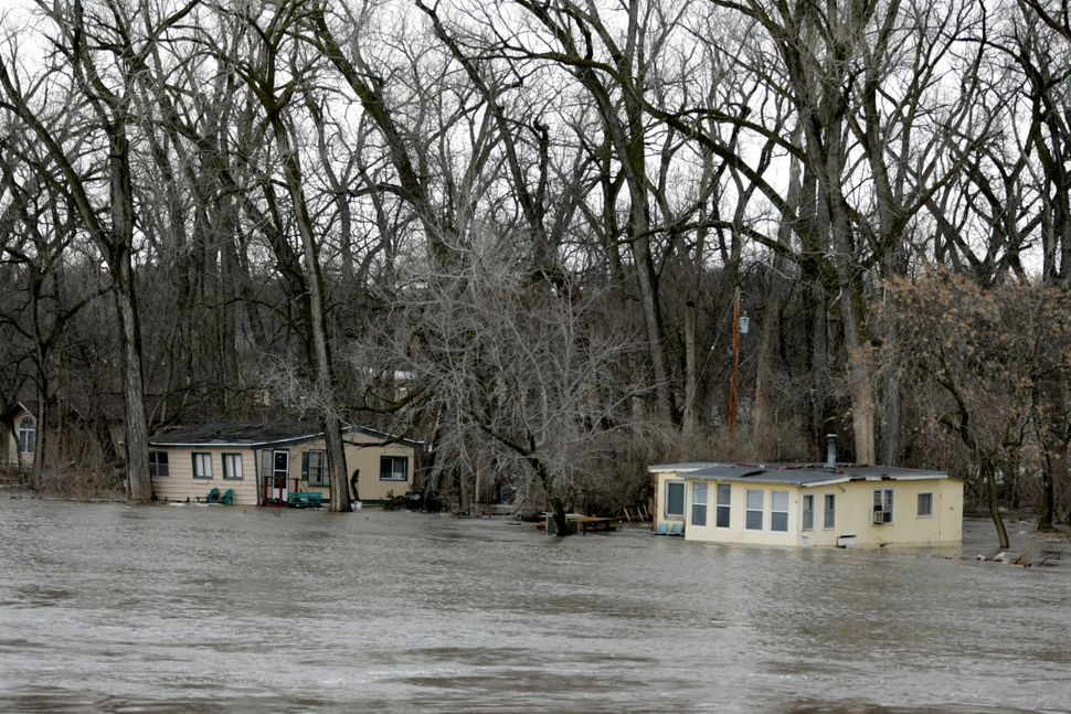 The rising waters of the Elkhorn River south of Arlington, Nebraska, Thursday, March 14, 2019, floods cabins. Evacuations for