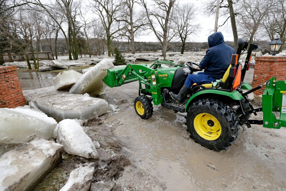 Chad Freeman works to clear thick ice slabs from his property in Fremont, Nebraska, Thursday, March 14, 2019, after the ice-c