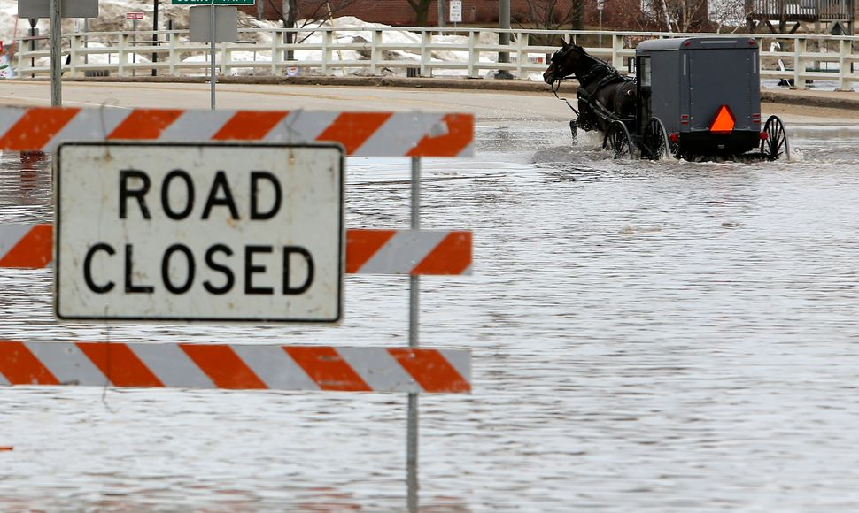 A man works his way through a flooded Galena Street as the Pecatonica River continues to rise in Darlington, Wisconsin, Thurs