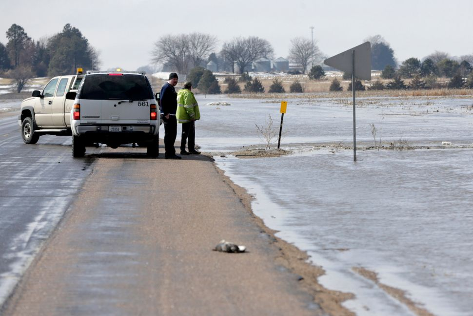 Men with the Nebraska Department of Roads monitor flooded highway 92, as the Cottonwood and Wahoo creeks overflow their banks