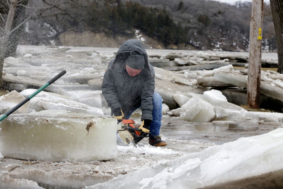 Jim Freeman tries to saw through thick ice slabs on his property in Fremont, Nebraska, Thursday, March 14, 2019, after the ic