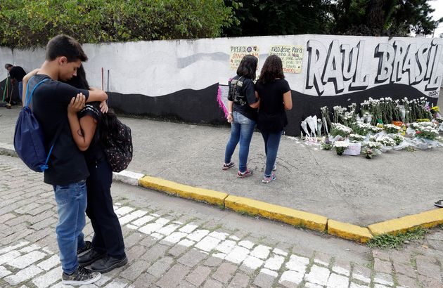 Students embrace outside the Raul Brasil state school one day after a mass shooting there in Suzano,...