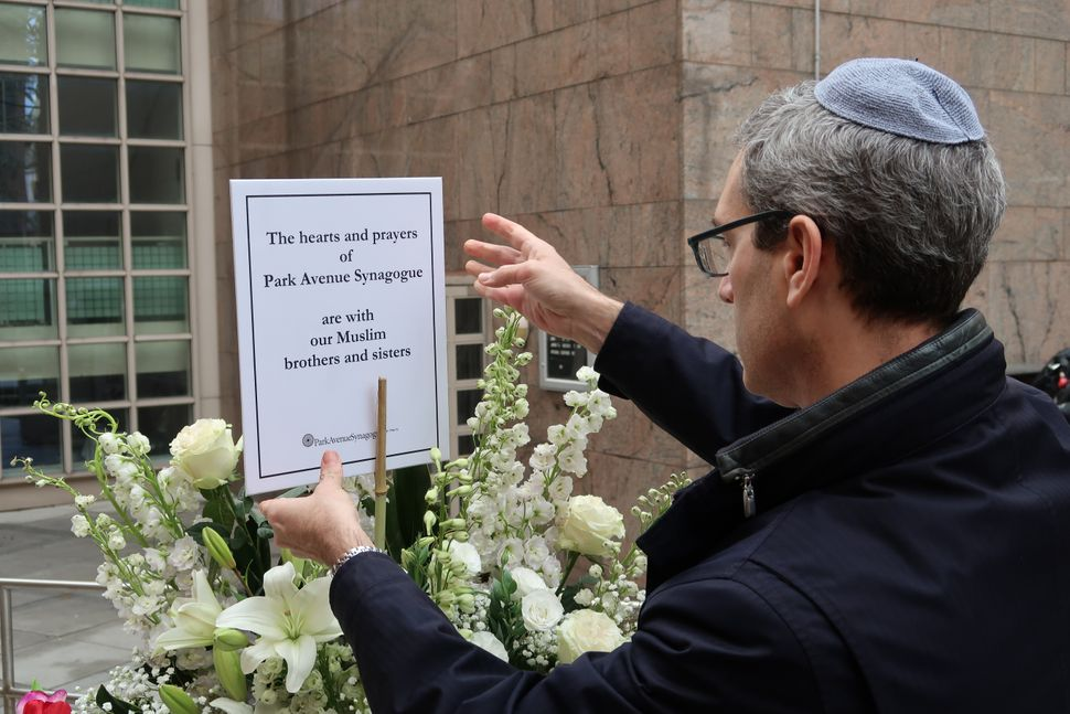 "A man places a support message reading, ""The hearts and prayers of Park Avenue Synagogue are with our Muslim brothers and sis"