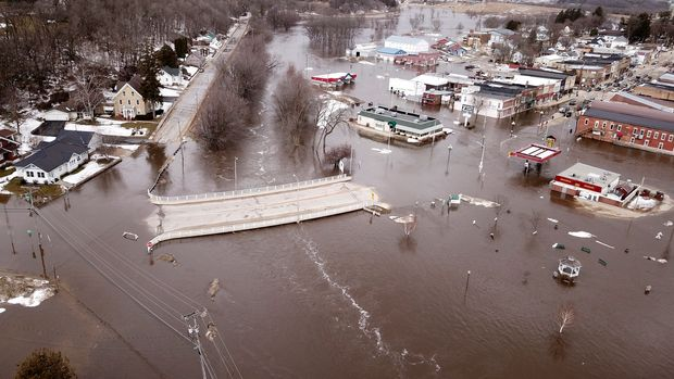 The swollen Pecatonica River spills into downtown Darlington, Wis., on Thursday March 14, 2019. The National Weather Service has issued a flood warning or flood watch for about two-thirds of the state. (Dave Kettering/Telegraph Herald via AP)