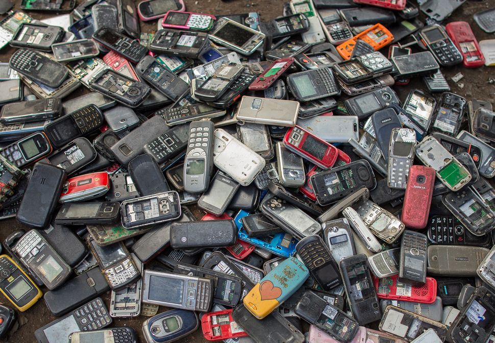 "Old mobile phones piled up at a scrapyard in Ghana's capital city, Accra. Last year, Apple alone sold <a href=""https://www.st"