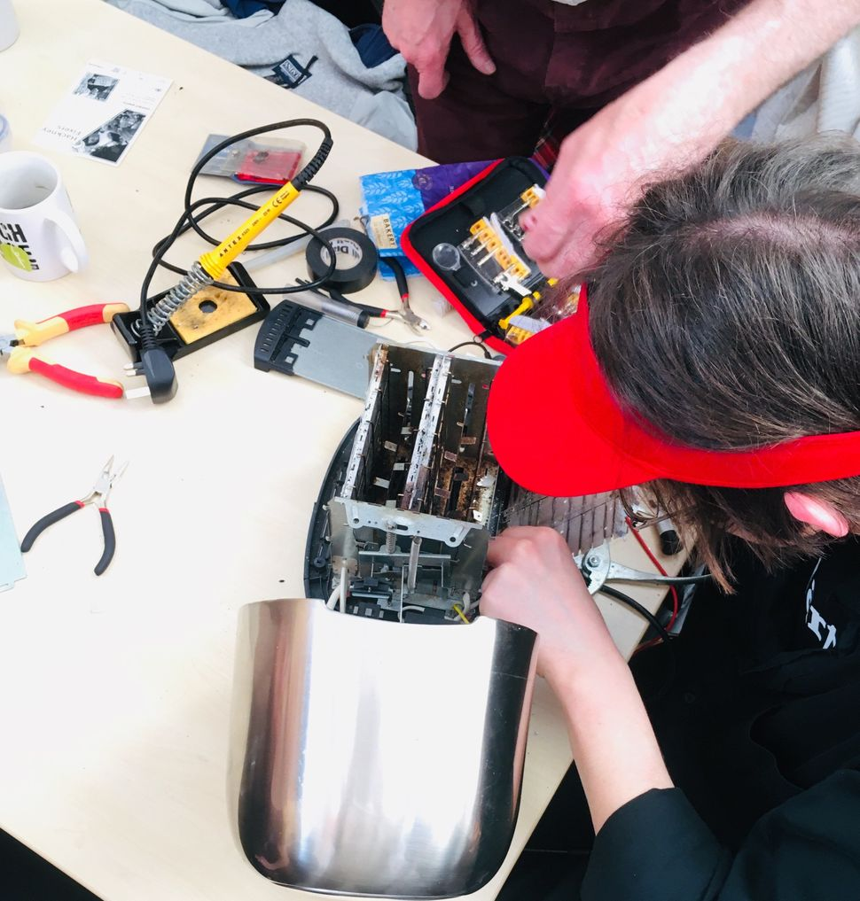"A volunteer ""fixpert"" assesses a broken toaster at the repair event I went to in London. The aim isn't just to fix the applia"