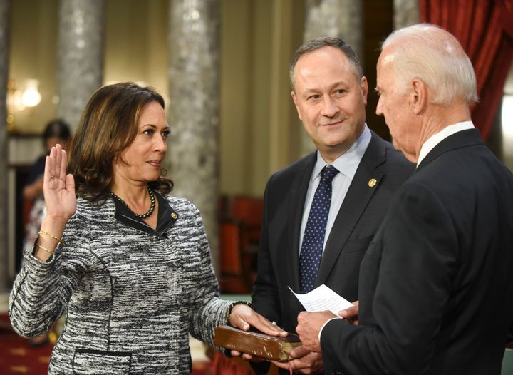 Vice President Joe Biden administers the Senate oath of office to Kamala Harris as her husband, Douglas Emhoff, holds the Bib