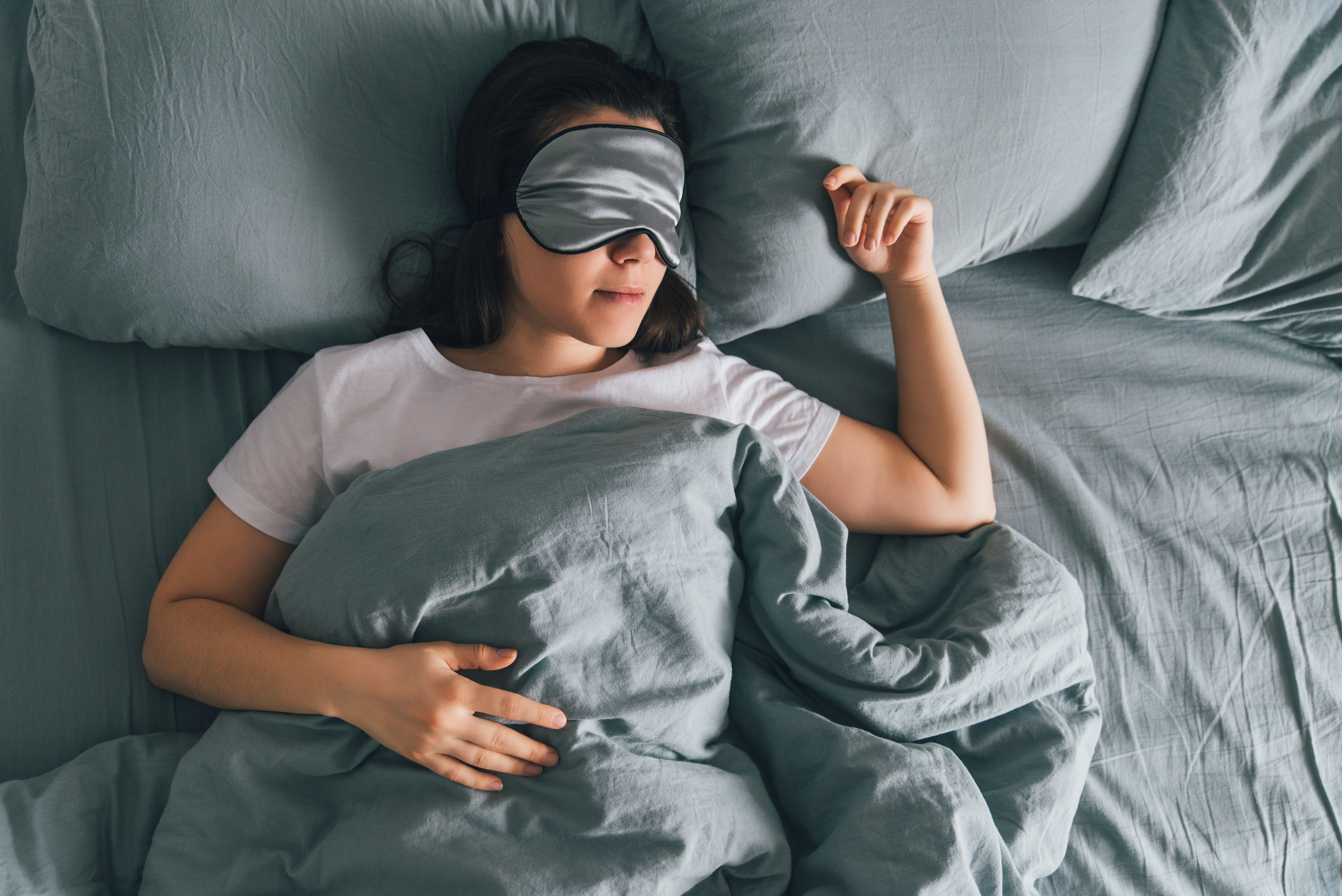 woman sleep in eye patch in grey bed. copy space
