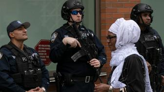 A woman leaves the Islamic Cultural Center of New York under increased police security following the shooting in New Zealand, Friday, March 15, 2019, in New York. (AP Photo/Mark Lennihan)
