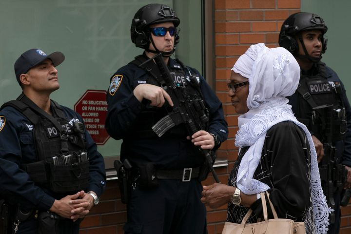 A woman leaves the Islamic Cultural Center of New York under increased police security following the shooting in New Zealand