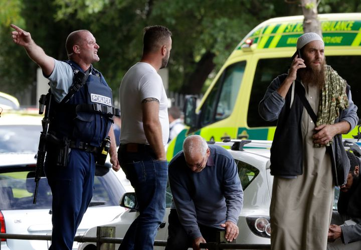 Police attempt to clear people from outside a mosque in central Christchurch, New Zealand, amid a mass shooting that claimed