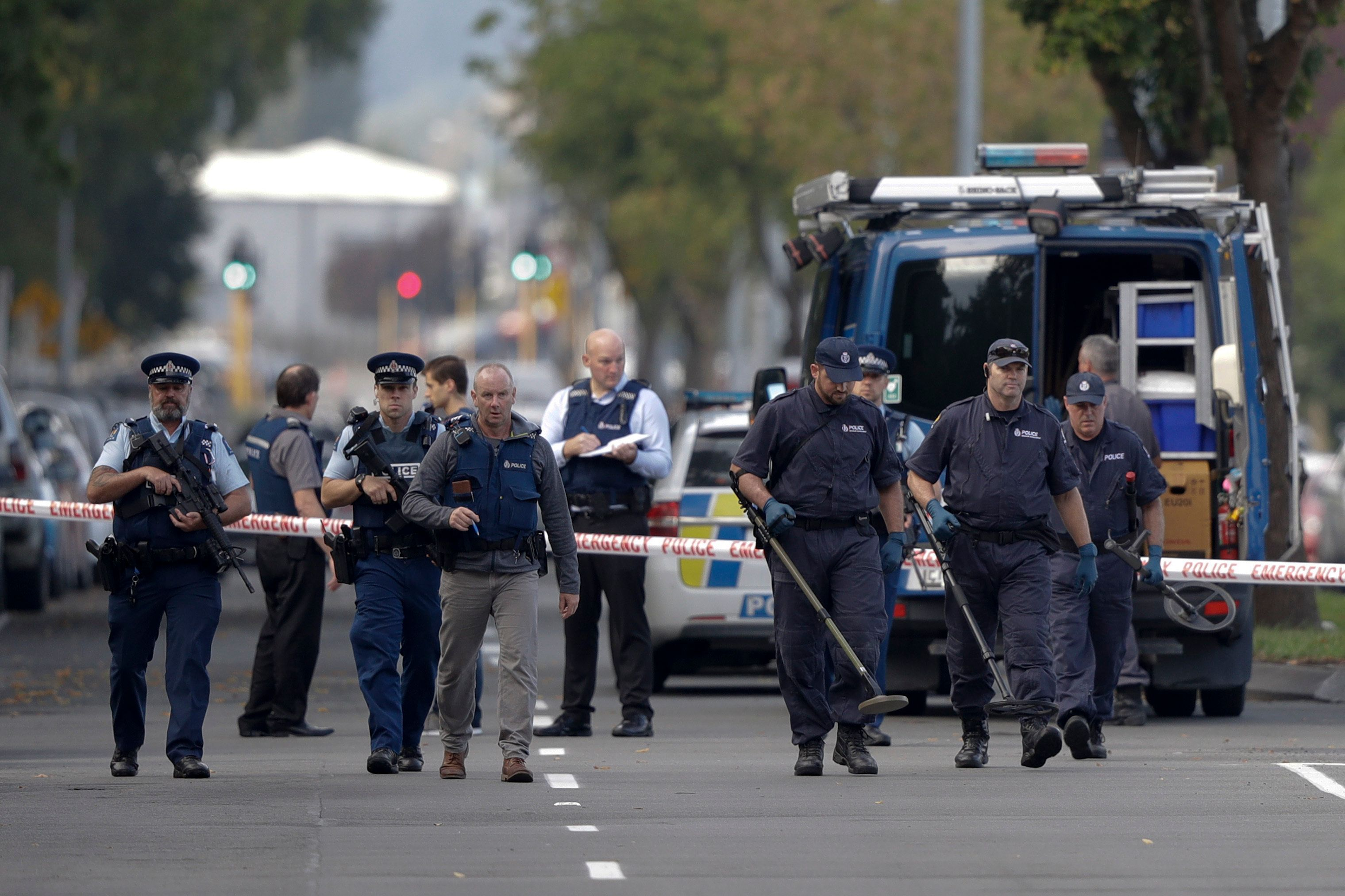 Police officers search the area near the Masjid Al Noor mosque, site of one of the mass shootings at two mosques in Christchurch, New Zealand, Saturday, March 16, 2019. (AP Photo/Mark Baker)