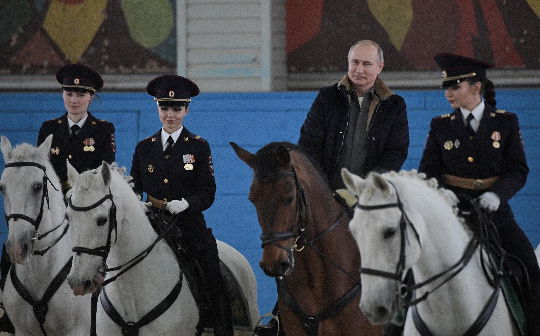 国際女性デーに合わせ、女性警察官らと乗馬するプーチン大統領=3月7日、モスクワ