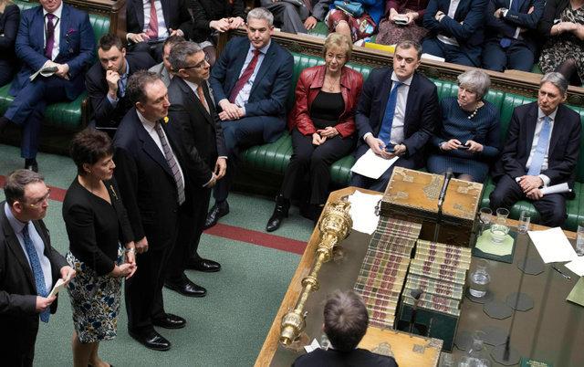 英議会下院で14日、EU離脱の延期をめぐる採決結果の発表を聞くメイ首相(右から2人目)=AP