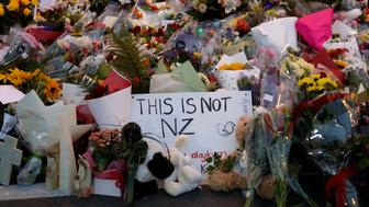 Mourners place flowers as they pay their respects at a makeshift memorial near the Masjid Al Noor mosque in Christchurch, New Zealand, Saturday, March 16, 2019. New Zealand's stricken residents reached out to Muslims in their neighborhoods and around the country on Saturday, in a fierce determination to show kindness to a community in pain as a 28-year-old white supremacist stood silently before a judge, accused in mass shootings at two mosques that left dozens of people dead.(AP Photo/Vincent Yu)