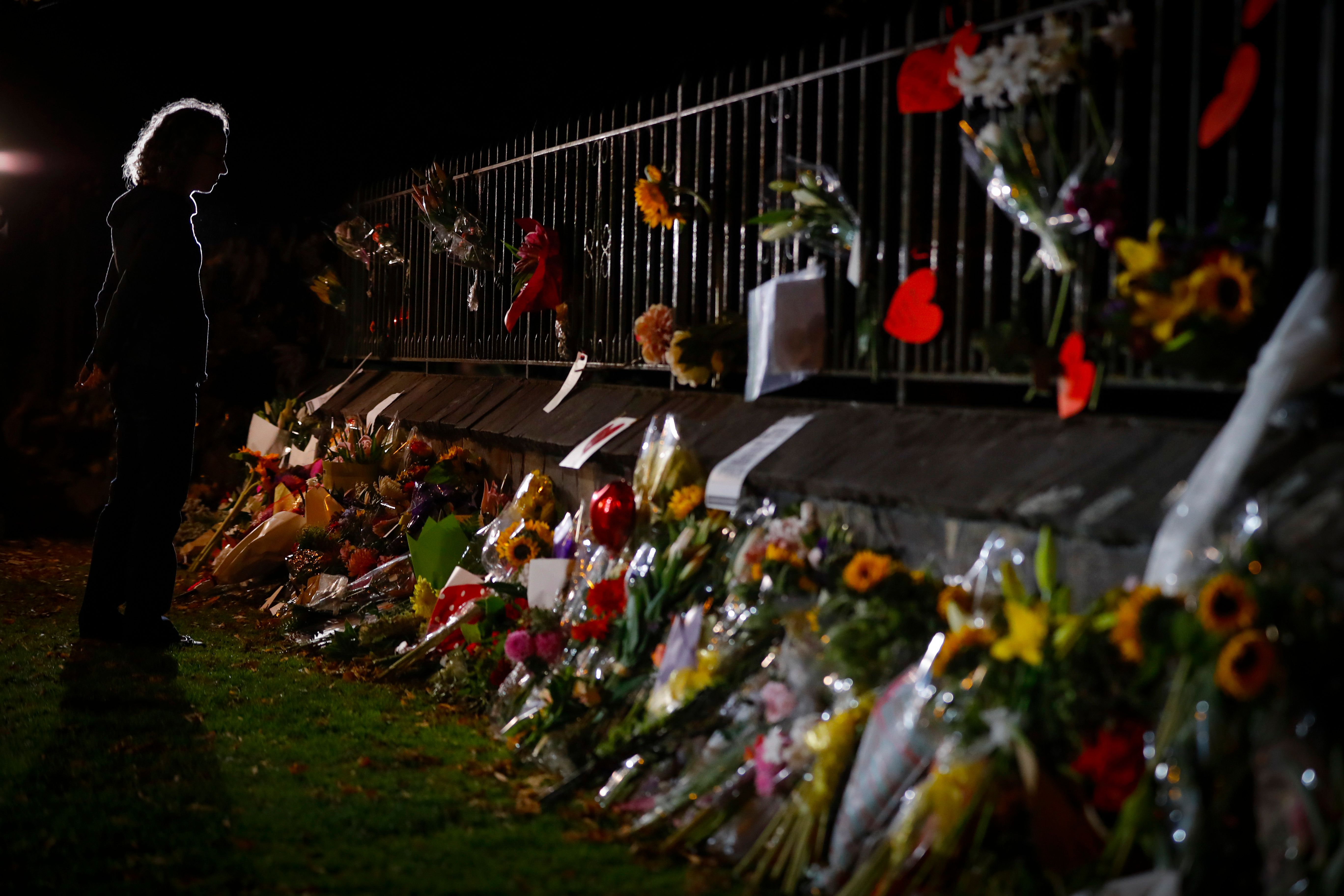 Mourners pay their respects at a makeshift memorial near the Masjid Al Noor mosque in Christchurch, New Zealand, Saturday, March 16, 2019. New Zealand's stricken residents reached out to Muslims in their neighborhoods and around the country on Saturday, in a fierce determination to show kindness to a community in pain as a 28-year-old white supremacist stood silently before a judge, accused in mass shootings at two mosques that left dozens of people dead. (AP Photo/Vincent Thian)