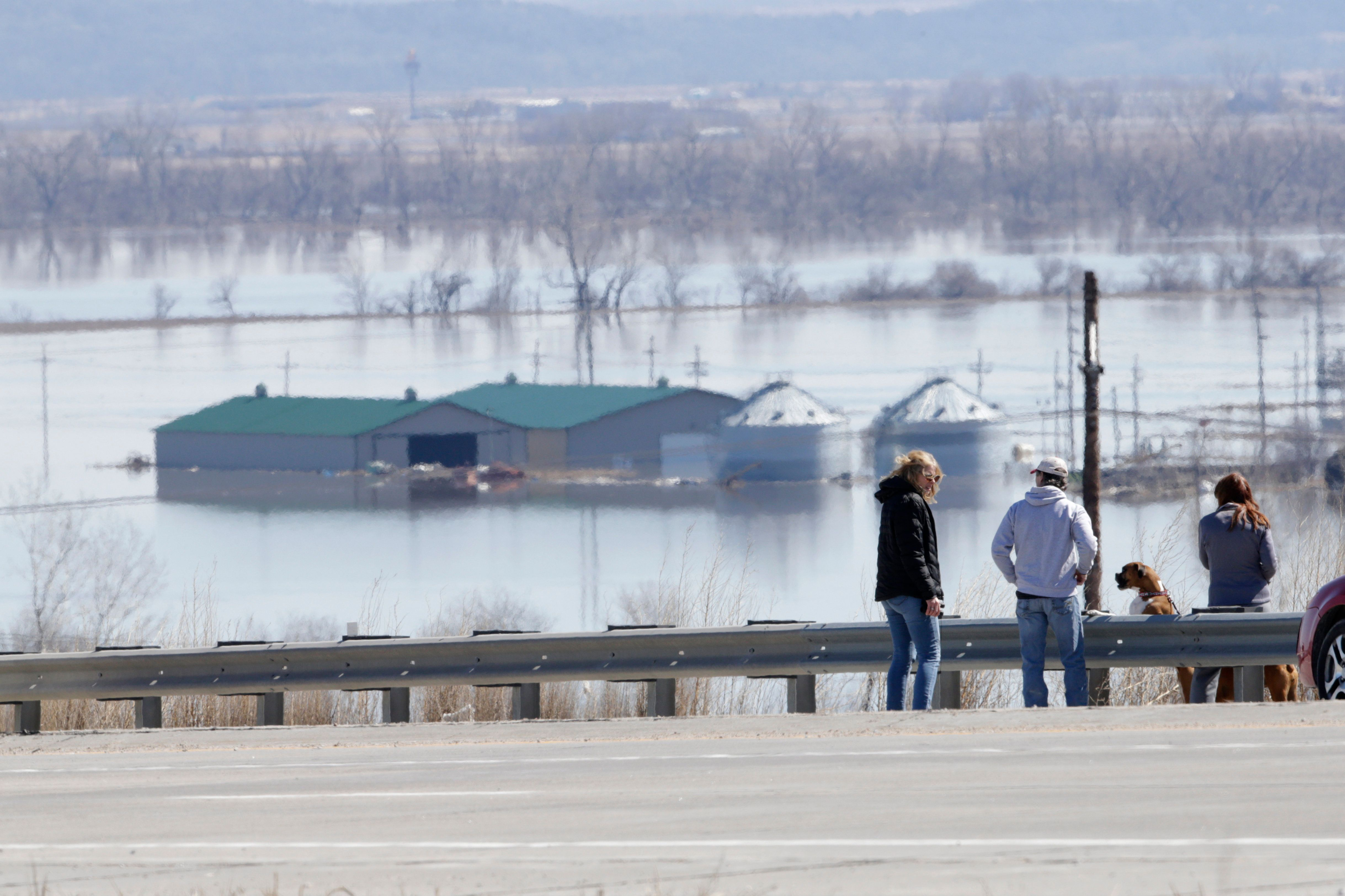 Travelers take in the overflowing Missouri River near Platteview, Neb., Saturday, March 16, 2019, as floodwaters from the Missouri River cover highways and surrounding farmland. Thousands of people have been urged to evacuate along eastern Nebraska rivers as a massive late-winter storm has pushed streams and rivers out of their banks throughout the Midwest. (AP Photo/Nati Harnik)