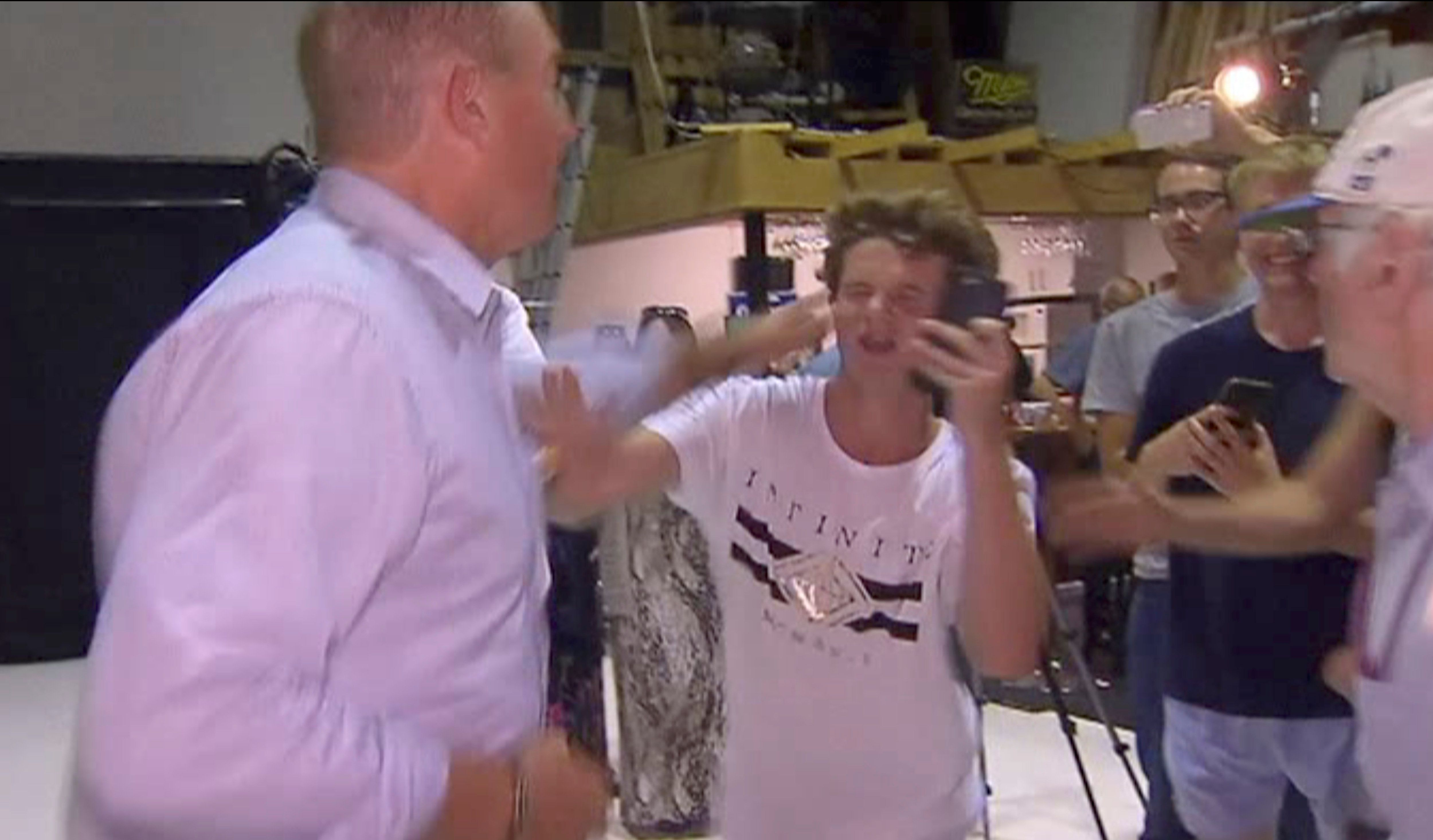"""In this image made from video, Senator Fraser Anning swipes at a teenager who broke an egg on his head while he was holding a press conference, Saturday, March 16, 2019, in Melbourne, New Zealand. Following the mass shootings on Friday, Anning came under sharp criticism over tweets including one that said: """"Does anyone still dispute the link between Muslim immigration and violence?"""" (AP Photo)"""