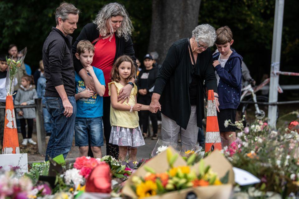 한 가족이 총기난사 테러 희생자들 앞에 조의를 표하고 있다. 뉴질랜드 크라이스트처치, 2019년