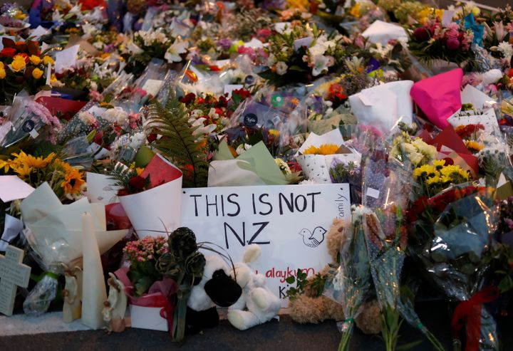Mourners place flowers as they pay their respects at a makeshift memorial near the Masjid Al Noor mosque in Christchurch, New