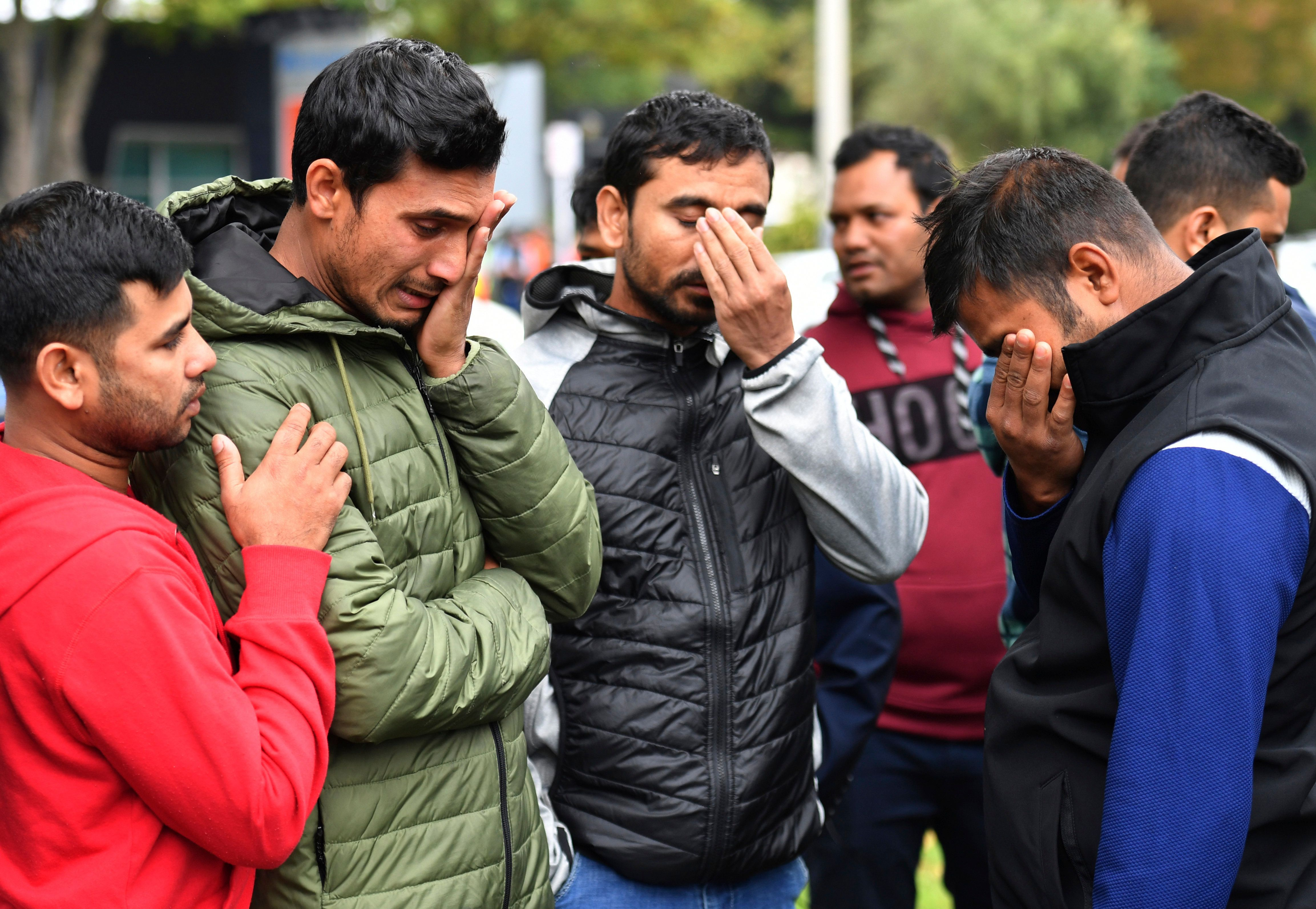 Friends of a missing man grieve outside a refuge center in Christchurch on