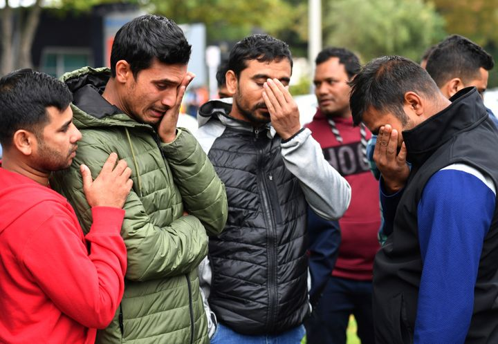 Friends of a missing man grieve outside a refuge center in Christchurch on Sunday.