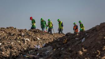 Workers walk to collect clothes and other materials, under the instruction of investigators, at the scene where the Ethiopian Airlines Boeing 737 Max 8 crashed shortly after takeoff on Sunday killing all 157 on board, near Bishoftu, or Debre Zeit, south of Addis Ababa, in Ethiopia Tuesday, March 12, 2019. Ethiopian Airlines had issued no new updates on the crash as of late afternoon Tuesday as families around the world waited for answers, while a global team of investigators began picking through the rural crash site. (AP Photo/Mulugeta Ayene)