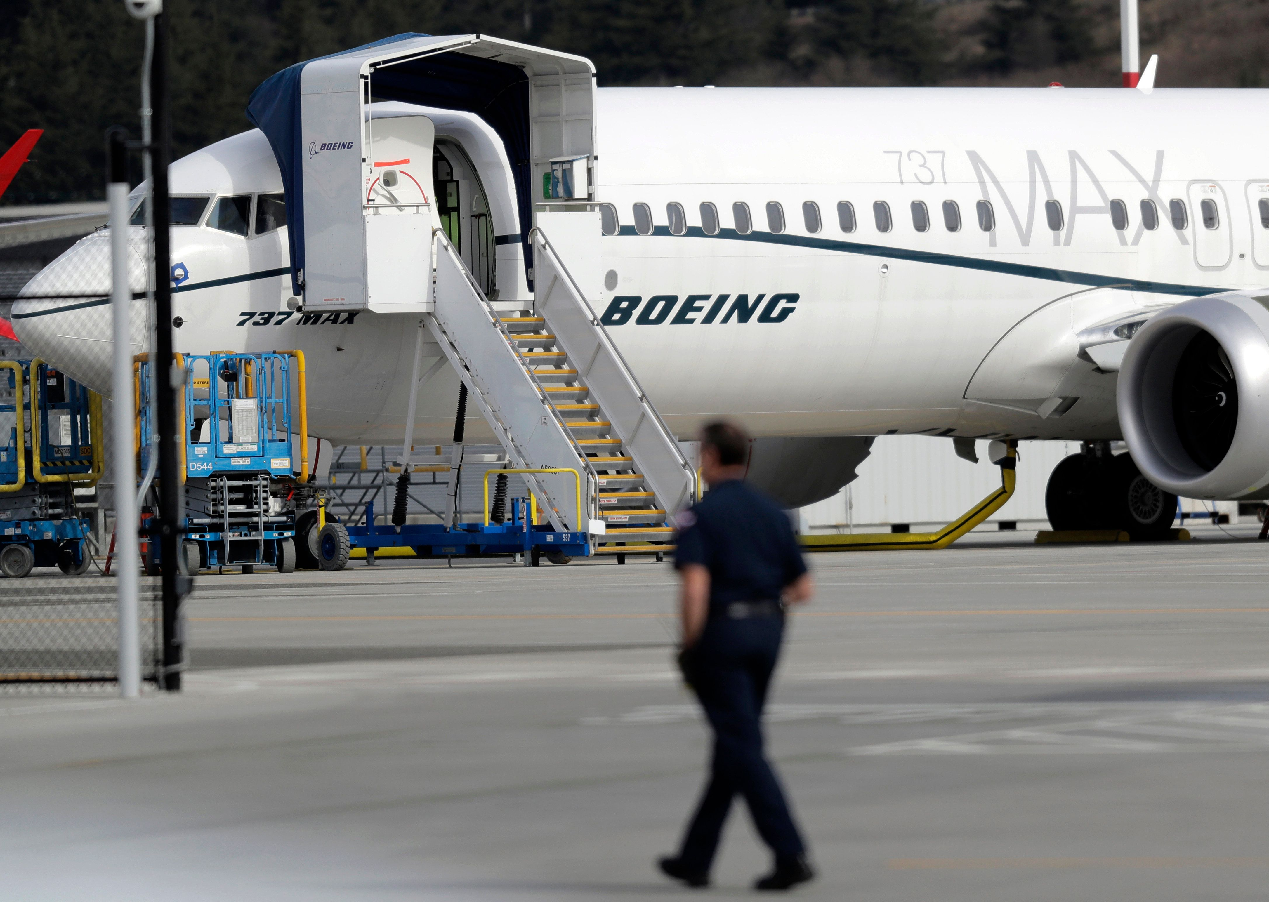 A worker walks next to a Boeing 737 MAX 8 airplane parked at Boeing Field, Thursday, March 14, 2019, in Seattle. The fatal crash Sunday of a 737 MAX 8 operated by Ethiopian Airlines was the second fatal flight for a Boeing 737 Max 8 in less than six months, and more than 40 countries, including the U.S., have now grounded the planes or refused to let them into their airspace. (AP Photo/Ted S. Warren)