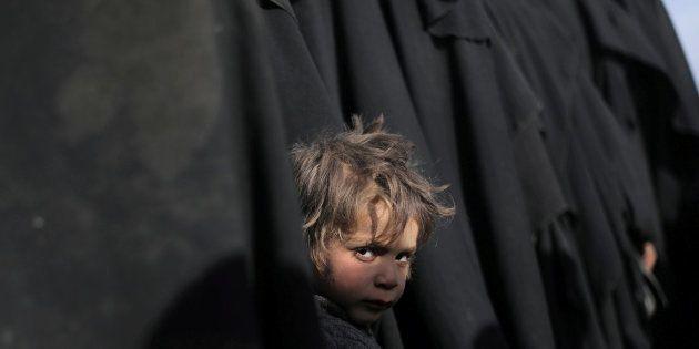 Un niño mira a la cámara en Baghouz, en la provincia de Deir Al Zor, tras escapar de la zona que el ISIS...