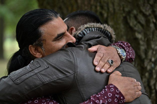 Abdul Aziz (L), 48, is greeted by a man who came to thank him for his bravery, during an interview with...