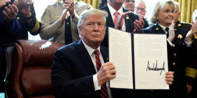 Donald Trump sostiene la carpeta con los documentos de su primer veto, hoy, en la Casa