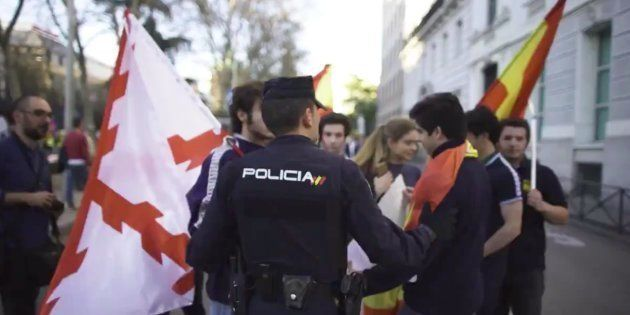 Un policía habla con varios jóvenes con banderas de