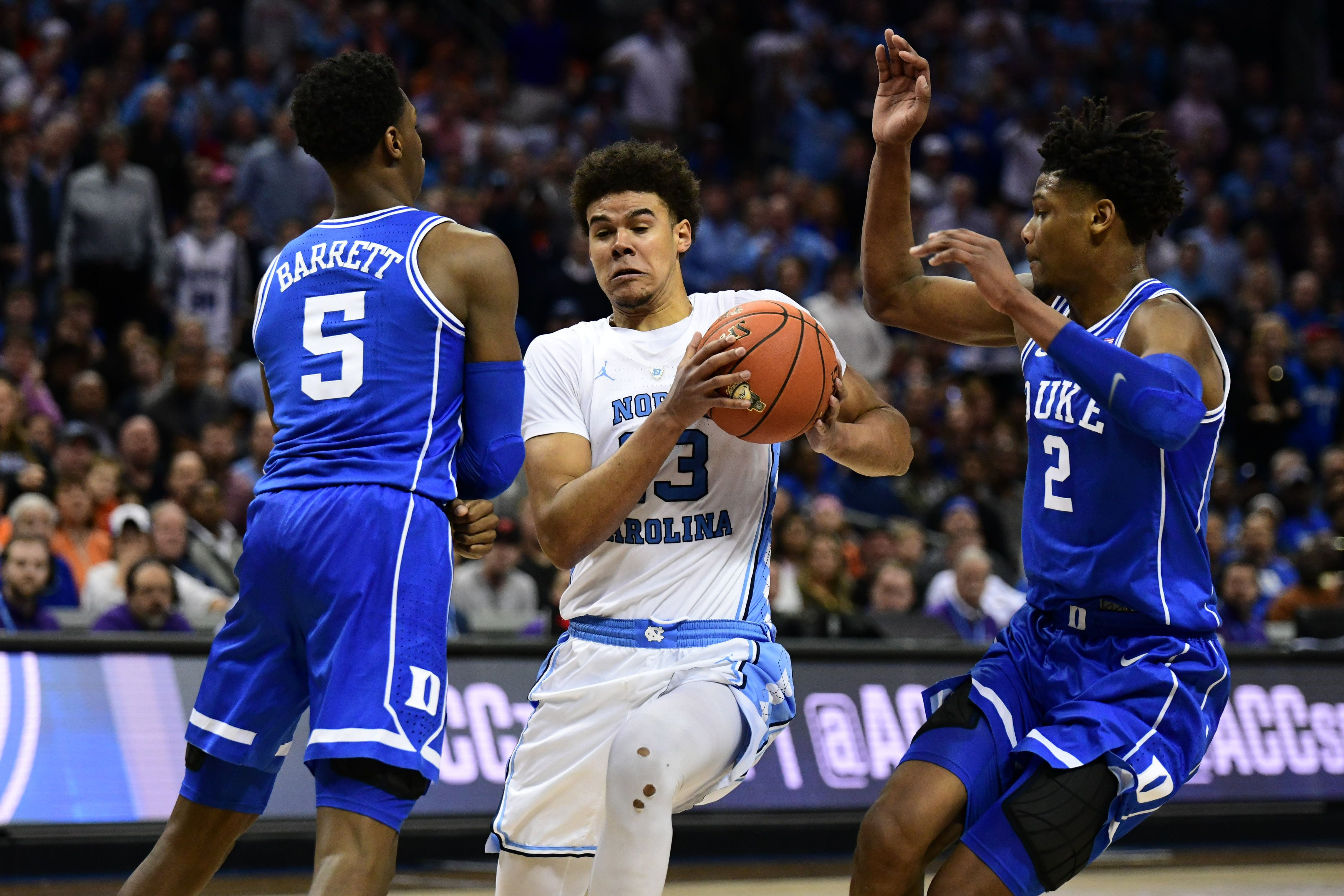 CHARLOTTE, NC - MARCH 15: North Carolina Tar Heels guard Cameron Johnson (13) drives through Duke Blue Devils forward RJ Barrett (5) and Duke Blue Devils forward Cam Reddish (2) during the ACC basketball tournament between the Duke Blue Devils and the North Carolina Tar Heels on March 15, 2019, at the Spectrum Center in Charlotte, NC. (Photo by William Howard/Icon Sportswire via Getty Images)