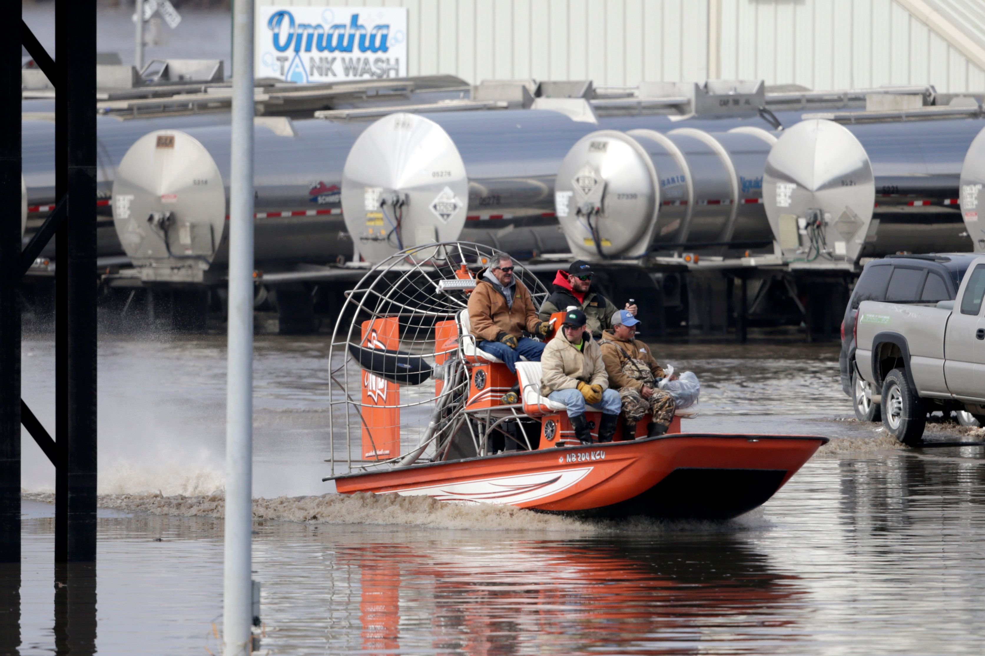 Gabe Schmidt, owner of Liquid Trucking, top right, travels by air boat with Glenn Wyles, top left, Mitch Snyder, bottom left, and Juan Jacobo, bottom right, as they survey damage from the flood waters of the Platte River, in Plattsmouth, Neb., Sunday, March 17, 2019. Hundreds of people remained out of their homes in Nebraska, but rivers there were starting to recede. The National Weather Service said the Elkhorn River remained at major flood stage but was dropping. (AP Photo/Nati Harnik)