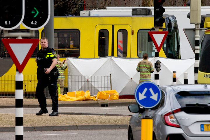 Rescue workers install a screen on the spot where a body was covered with a white blanket following a shooting in Utrecht, Ne