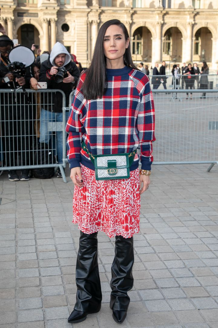 Jennifer Connelly wears a skirt over pants outside the Louis Vuitton show in Paris, 2019.