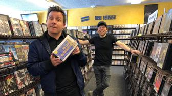 Local documentary filmmakers Taylor Morden, left, and Zeke Kamm, pose at the last Blockbuster on the planet in Bend, Ore., on Monday, March 11, 2019, with a promotional VHS tape of their upcoming documentary about the store titled The Last Blockbuster. When a Blockbuster in Perth, Australia, shuts its doors for the last time on March 31, the store in Bend, Ore., will be the only one left on Earth, and most likely in the universe. (AP Photo/Gillian Flaccus)