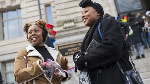 Sisters Jackie, left, and Bria Cook, hand out marijuana cigarettes at a rally in Washington, D.C, to push for changes to the