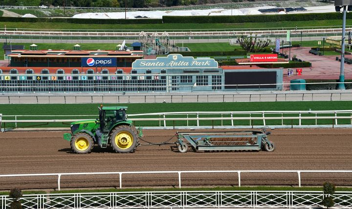 A tractor is driven at the Santa Anita Racetrack where races were suspended after multiple horse deaths. The track has since