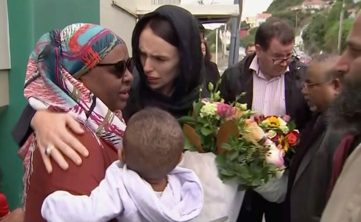 In this image made from video, New Zealand's Prime Minister Jacinda Ardern, center, hugs and consoles a woman as she visited