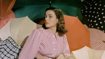 Actress Gene Tierney surrounded by open umbrellas, wearing a peppermint-striped playsuit with long sleeves and bare midriff. (Photo by Horst P. Horst/Condé Nast via Getty Images)