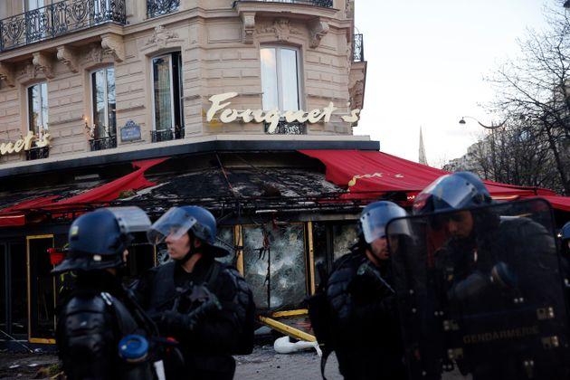Agentes antidisturbios, ante el restaurante Fouquet´s, cuya terraza quedó calcinada este...