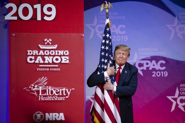 Donald Trump, abrazando una bandera de EEUU, en laConferencia de Acción Conservadora del...