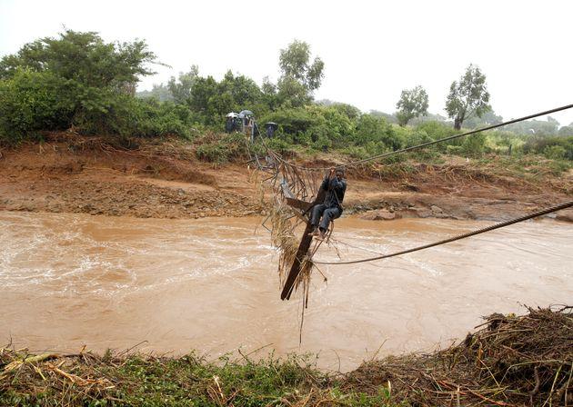 Un homme traverse une rivière inondée à Chimanimani, au Zimbabwe, après le...