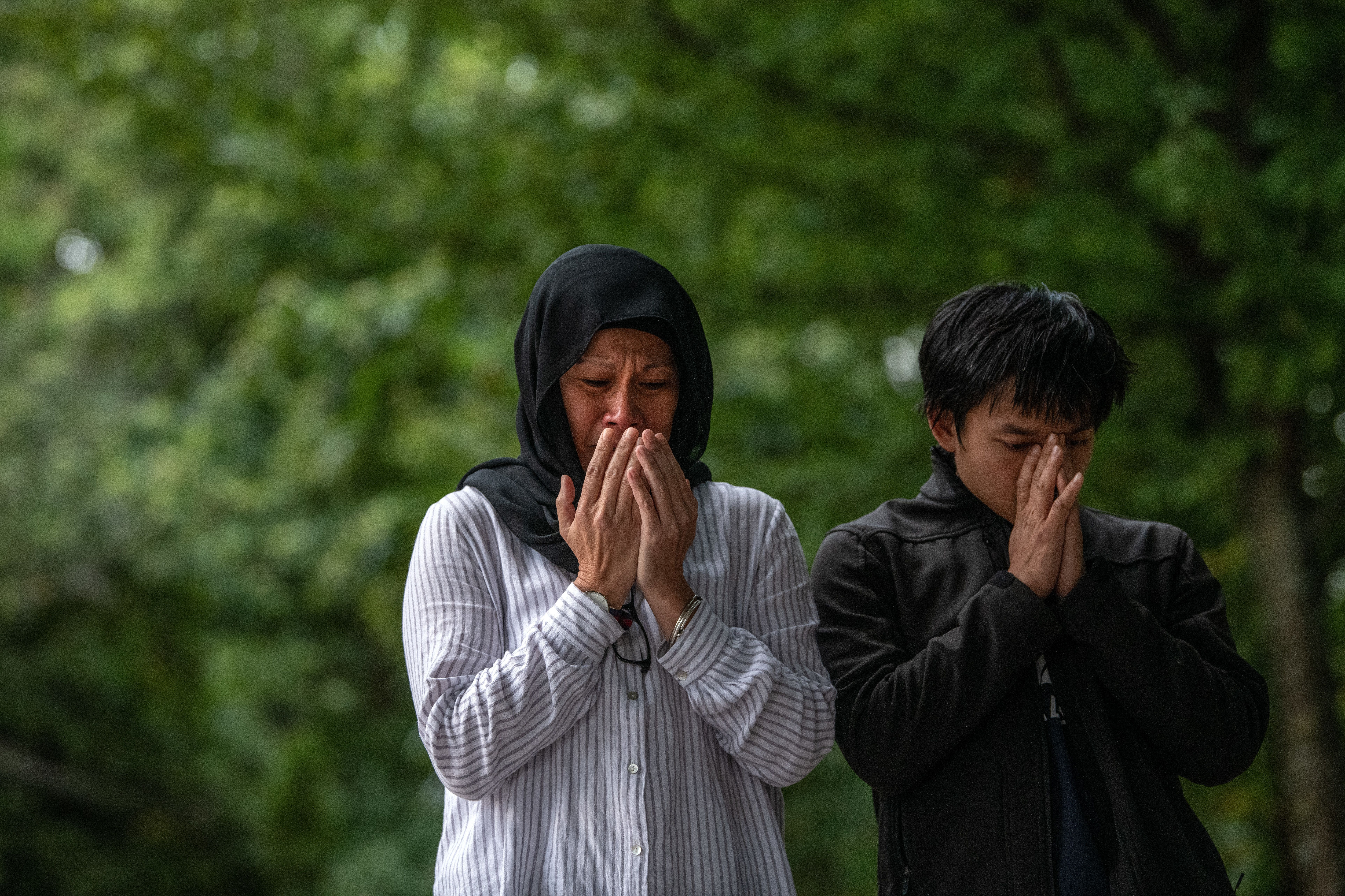CHRISTCHURCH, NEW ZEALAND - MARCH 19: People pray next to flowers and tributes near Al Noor mosque on March 19, 2019 in Christchurch, New Zealand. 50 people were killed, and dozens are still injured in hospital after a gunman opened fire on two Christchurch mosques on Friday, 15 March.  The accused attacker, 28-year-old Australian, Brenton Tarrant, has been charged with murder and remanded in custody until April 5. The attack is the worst mass shooting in New Zealand's history. (Photo by Carl Court/Getty Images)