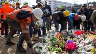Construction workers who witnessed Monday's shooting incident in a tram put flowers at the site in Utrecht, Netherlands, Tuesday, March 19, 2019. A gunman killed three people and wounded others on a tram in the central Dutch city of Utrecht Monday March 18, 2019. (AP Photo/Peter Dejong)