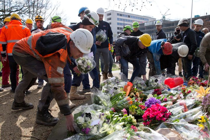Construction workers who witnessed Monday's shooting incident in a tram put flowers at the site in Utrecht, Netherlands, on T
